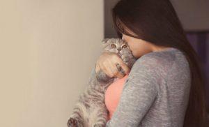 Mulher abraçando gato